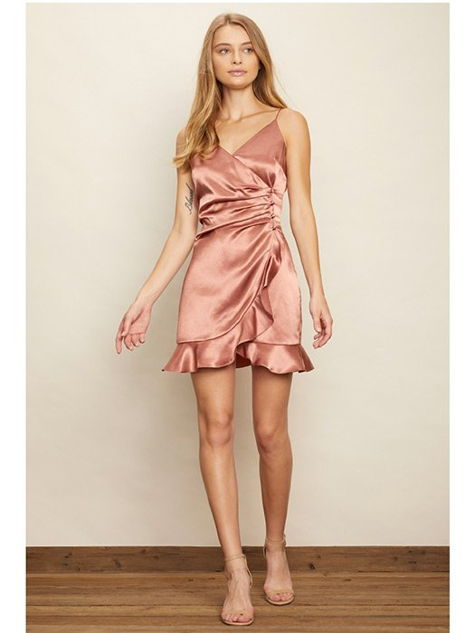 Satin surplice mini dress featuring ruffled bottom hem and pleated detail with b